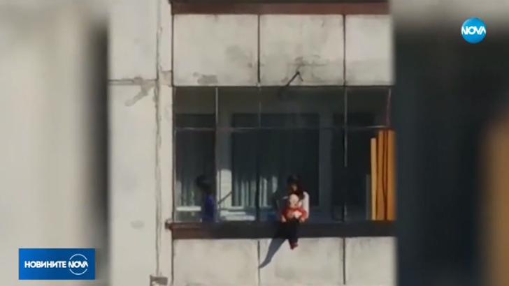 Резултат с изображение за Жена провесва малко дете през балкон